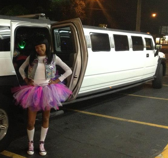 Happy little Birthday Girl poses with Hummer Limo