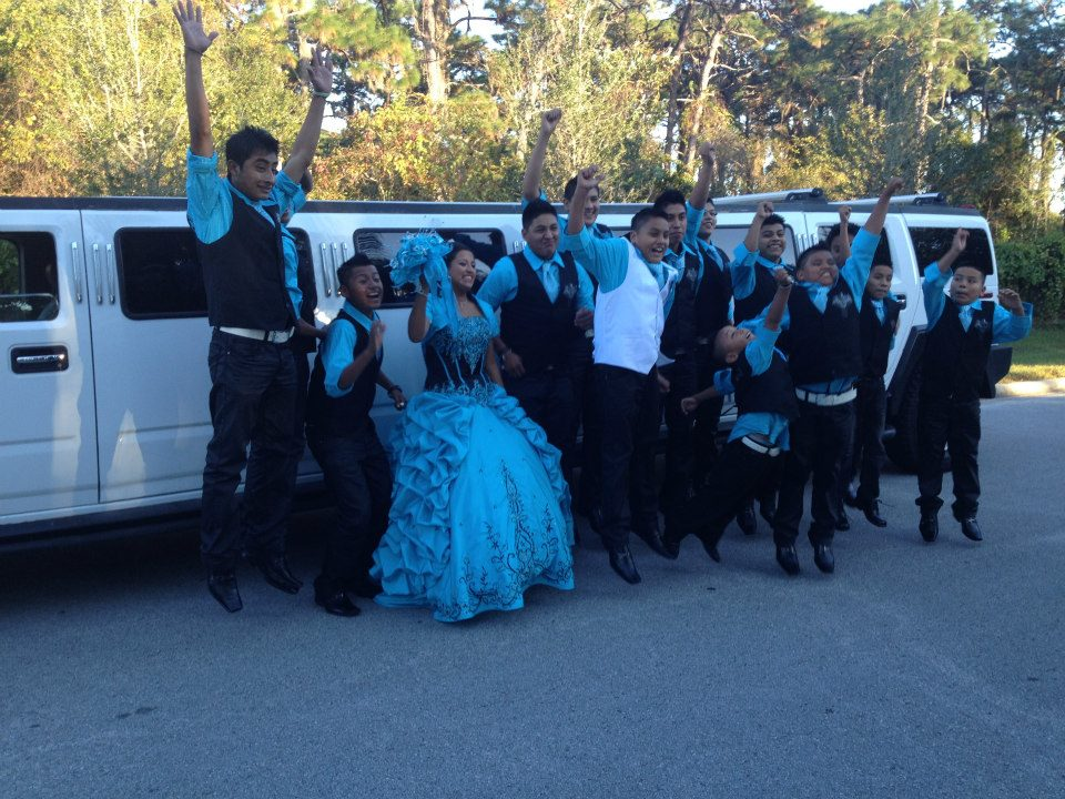 Quinceanera group celebrating outside limo