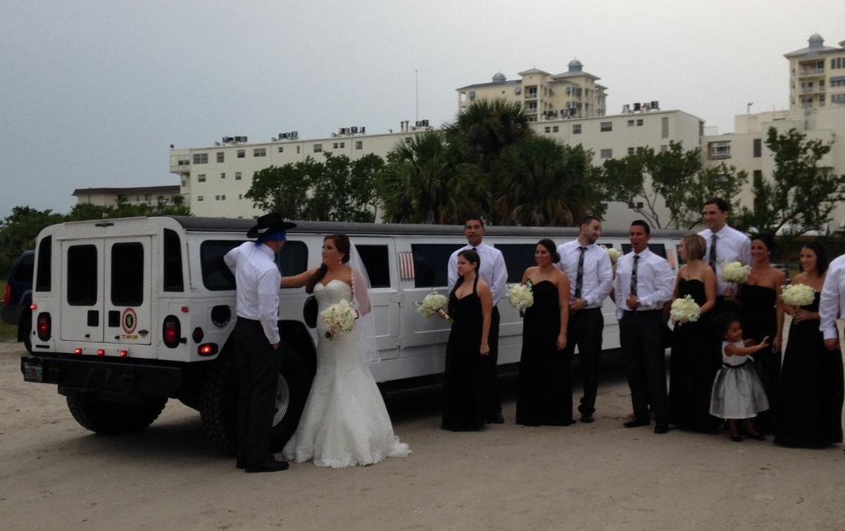 Wedding party poses next to Hummer H1 Limo