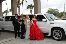 Prom group poses next to Escalade Limo